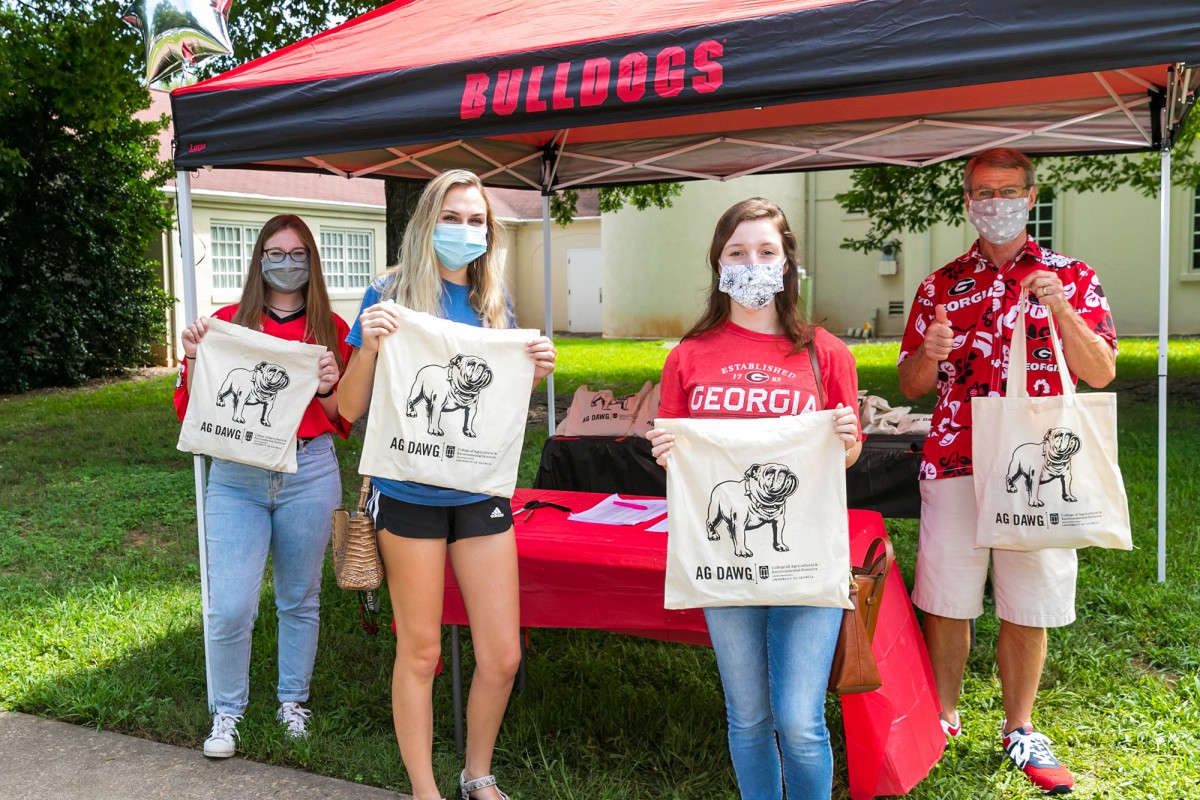 Katie Fife (far left) and Doug Bailey, assistant dean for academic affairs, (far left) hand out Ag Dawg swag bags at Ag Dawg Kickoff.