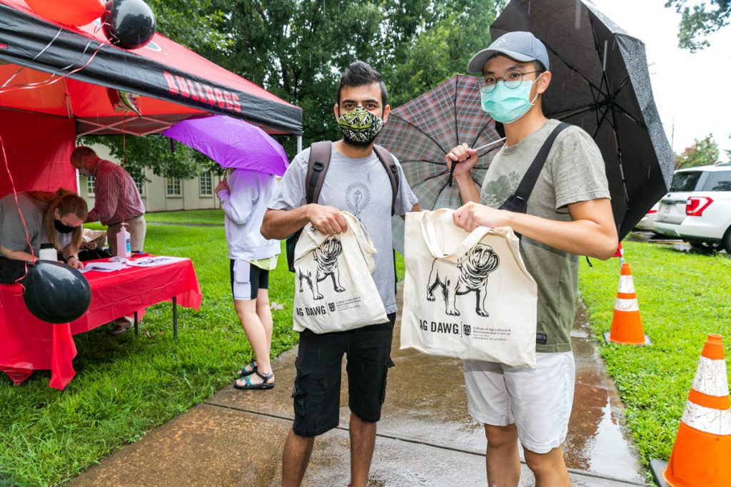 Two students brave the rain to pick up their Ag Dawg swag bag.